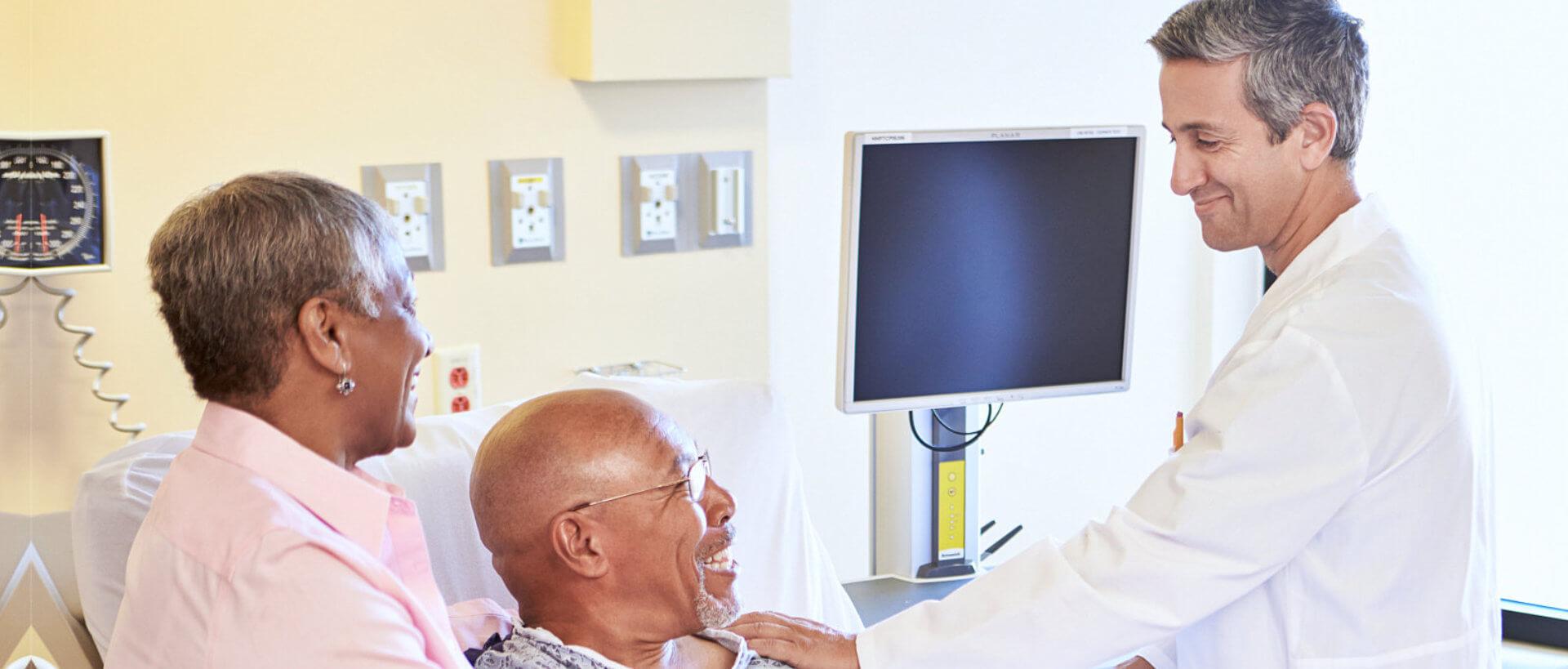 happy senior couple talking to doctor